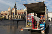 A van driver bends to check delivery items from the back of his vehicle opposite the Renaissance Cloth Hall on Rynek Glowny market square, on 23rd September 2019, in Krakow, Malopolska, Poland.