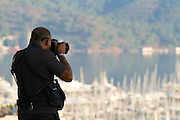 A photographer photographing sailing boats in the early morning light.