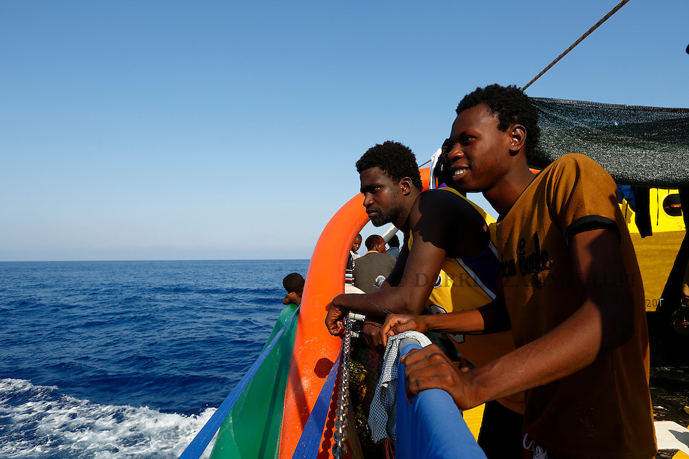 Migrants look out to sea from the stern of the Medecins san Frontiere (MSF) rescue ship Bourbon Argos somewhere between Libya and Sicily August 8, 2015.  Some 241 mostly West African migrants on the ship are expected to arrive on the Italian island of Sicily on Sunday morning, according to MSF.<br /> REUTERS/Darrin Zammit Lupi <br /> MALTA OUT. NO COMMERCIAL OR EDITORIAL SALES IN MALTA