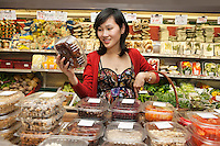 Beautiful young woman looking at produce in package in market