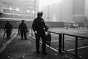 Three riot police officers walk through an empty carpark, Scumoween, Whitgift Street, Lambeth, London, UK, 31 October, 2015