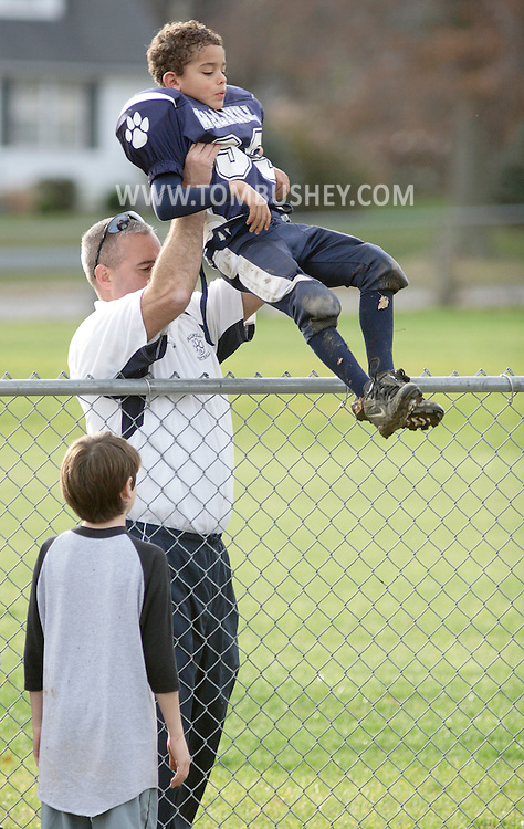 Middletown, NY - A man lifts a boy wearing a football uniform over a fence so he can get to the field on Nov. 14, 2009.