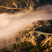 A photo of early morning fog blowing over an old bridge on California highway 40 at sunrise
