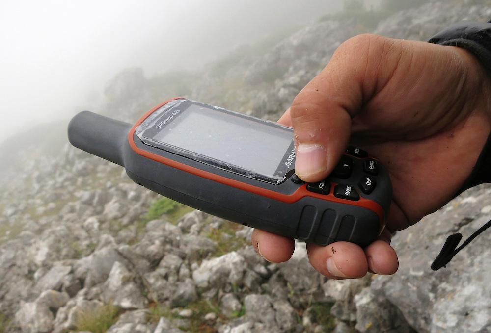 Using the GPS for orientation in the mist, trying to find the approach path to the summit of Maglic mountain, Bosnia and Herzegovina.