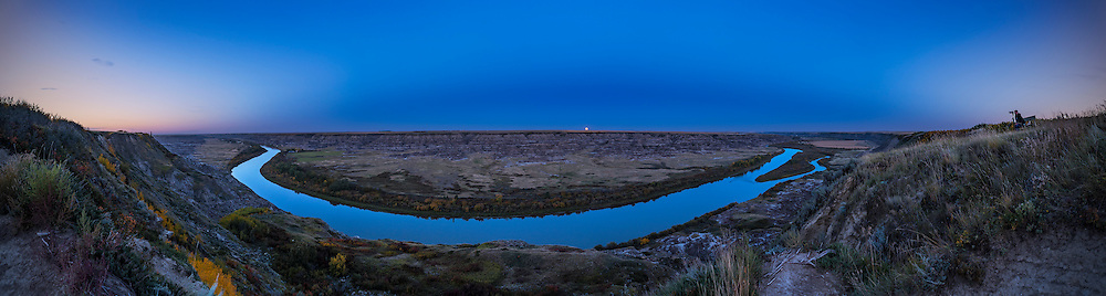 The Harvest Moon of September 16, 2016, rising over the badlands of the Red Deer River valley from Orkney Viewpoint, north of Drumheller, Alberta. The blue arc of the rising shadow of the Earth projected onto the upper atmosphere curves across the sky, mirroring the curving arc of the river below. A photographer at far right captures the scene of the moonrise over the Badlands. <br /> <br /> This is a 7-section single-tier panorama with the 20mm Sigma lens and Nikon D750 at ISO 100. Stitched with Adobe Camera Raw.
