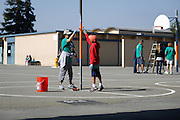 Tiffany Nguyen and Alan Mai, 10, paint a tetherball pole during Comcast Cares Day at Curtner Elementary School in Milpitas, California, on April 27, 2013. (Stan Olszewski/SOSKIphoto)