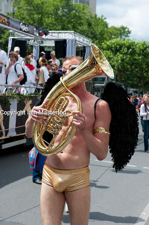 Man wearing angel wings and playing horn at  the Christopher Street Day Parade in Berlin Germany 2011