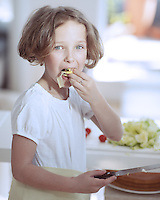 Young girl eating salad whilst holding knife in kitchen