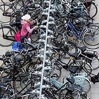 Nederland Rotterdam 23-09-2009 20090923 Serie over onderwijs,   openbare scholengemeenschap mavo, havo en vwo.  Meisje plaatst haar fiets in het fietsenrek, gezonde gewoonte, zij gaat op de fiets naar school.                                              .Foto: David Rozing