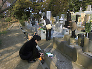 Japan Tending to a family memorial grave