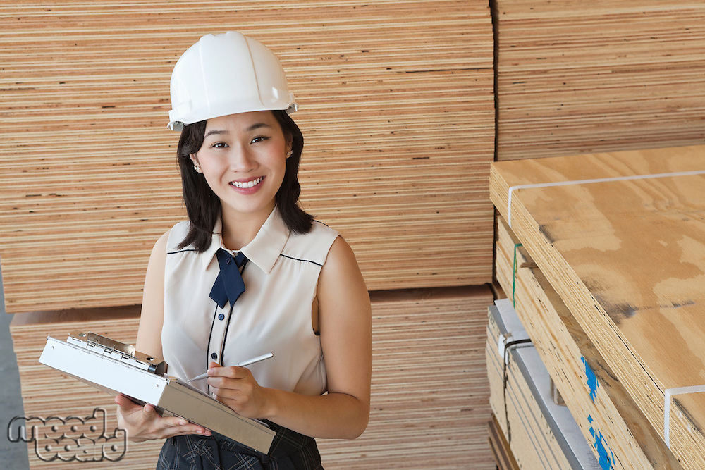 Portrait of young female industrial worker writing on clipboard with wooden planks in background