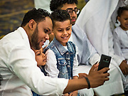 04 JUNE 2019 - DES MOINES, IOWA: A man and his sons take selfies before Eid al Fitr services in the Iowa Events Center in Des Moines Tuesday. About 3,000 people were expected to attend the annual community wide celebration of Eid al Fitr which marks the end of Ramadan, the Muslim month of fasting. According to the event organizers, there are about 15,000 Muslims in the Des Moines area.           PHOTO BY JACK KURTZ