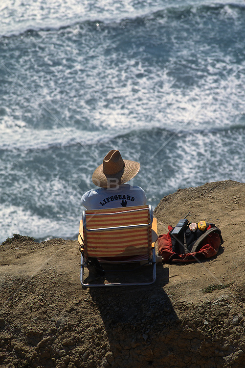 Back of a lifeguard sitting on a cliff by the ocean in San Diego, CA