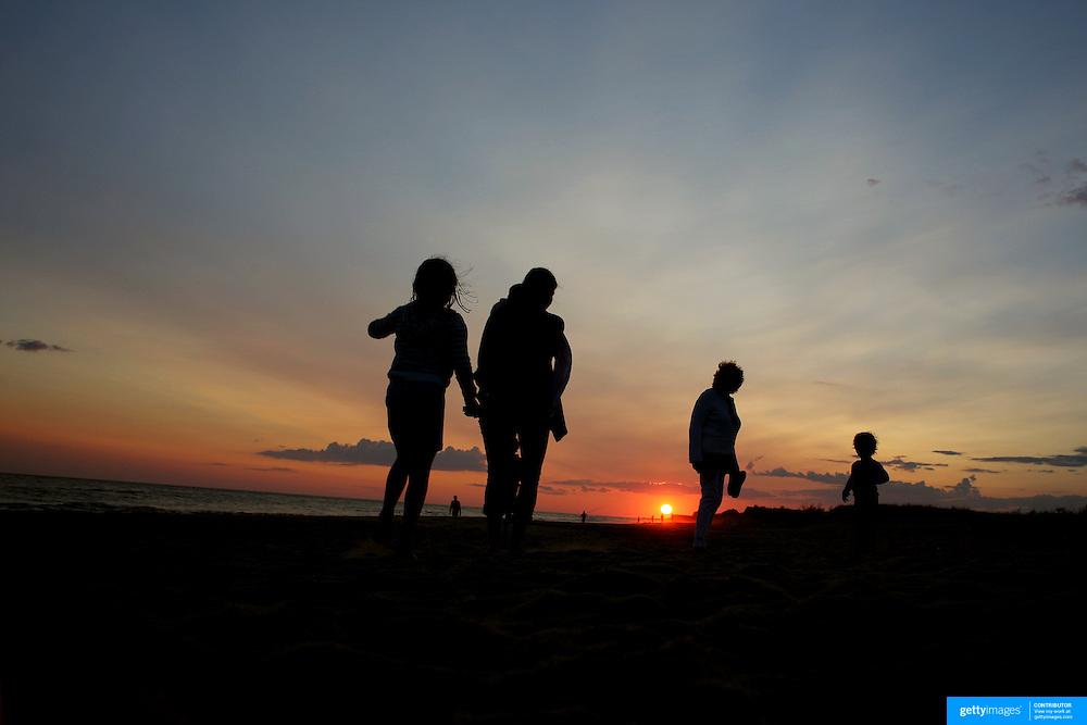 A family walk along the beach at sunset in the height of summer on Cisco Beach, Nantucket, Nantucket Island, Massachusetts, USA. Photo Tim Clayton