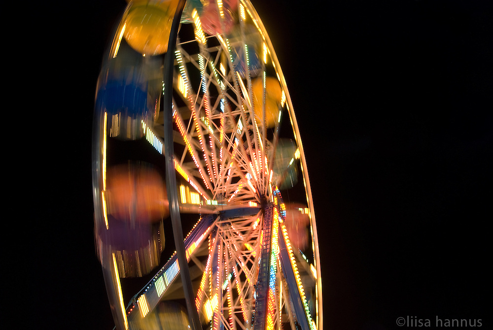 The Westcoast Wheel, a colourful ferris wheel spins in the night at the Pacific National Exhibition in Vancouver, British Columbia. Standing at 90 feet, the Westcoast Wheel offers spectacular views of the mountains, city and surrounding areas.