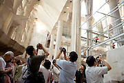 Asian tourists photographing inside la Sagrada Familia Barcelona Spain