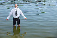 Businessman standing in lake, eyes closed