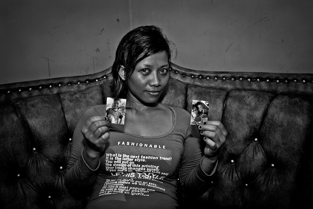 A brothel worker shows pictures of her son.