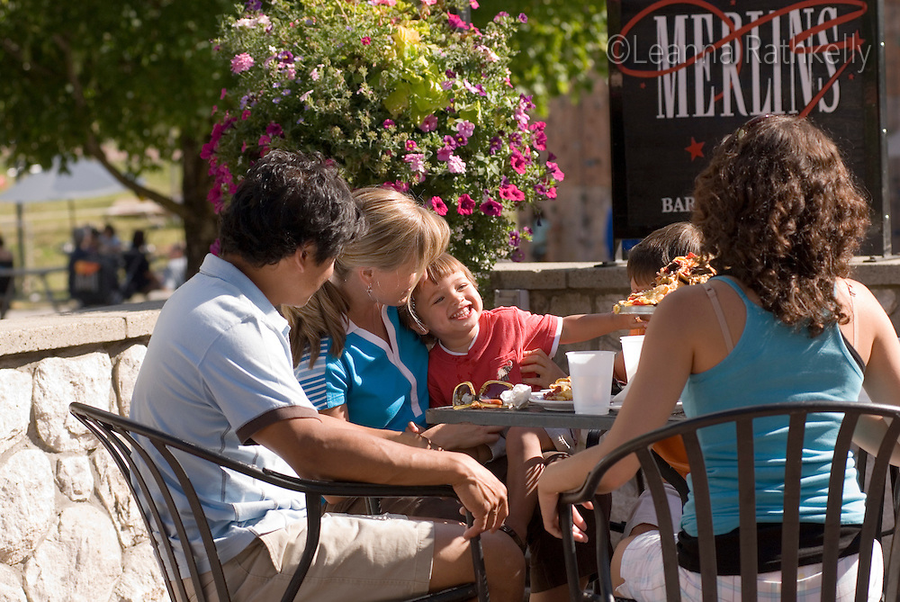 A family enjoys an outdoor lunch on the patio at Merlins restaurant, at the base of Blackcomb Mountain, Whistler, BC Canada.
