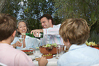 Family with children (6-11) dining in garden man pouring wine
