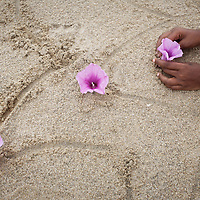 Vijitha places flowers in the sand on the beach close to the location of her mother's death in the tsunami. <br /><br />These photographs encompass four years in the lives of two families of children from South India who lost their mothers to the Asian tsunami. Following that momentous event in 2004, the five Krishnamurthy sisters from Puddupettai went to live in the Cuddalore Government Special Home for Tsunami Children. And Vijitha and Vijyashree Viswanathan, after an initial brief spell at the same home, now live with their father and his new wife in the nearby fishing village of Thalanguda. <br /><br />Each child affected by the tsunami had to adapt to changed circumstances and cope with emotions no one in their family could have possibly anticipated. The younger children seemed to adjust more quickly than their older siblings. And, while grief rendered some silent, in others it provoked a real sense of anger. Some became withdrawn while others craved attention and resorted to disruptive behavior. For all of the children, the experience of losing a parent seemed to strengthen the bond they shared with their brothers and sisters. <br /><br />The loss of a parent meant that some of the children photographed in this project inherited responsibilities that, while often a burden, provided a distraction from their own painful emotions. Sivaranjini Krishnamurthy lost her mother to the tsunami and then, together with her four younger sisters was abandoned by her father. At eleven years of age she took on the role of a mother to her younger sisters. Though she attends school and receives the support of orphanage staff, Sivaranjini has sacrificed much of her own childhood to take care of them. <br /><br />For Sivaranjini and the other children whose experiences are presented here, the tsunami is a defining event in their lives; the terrible personal upheaval they have suffered will inevitably shape all of their futures. <br /><br />Photo: Tom Pietrasik<br />Tamil Nadu, In