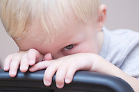 Blonde toddler peeks over chair looking at camera