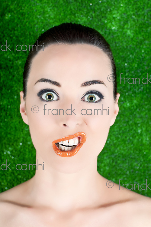 Closeup portrait of a woman funny grimacing  isolated on green
