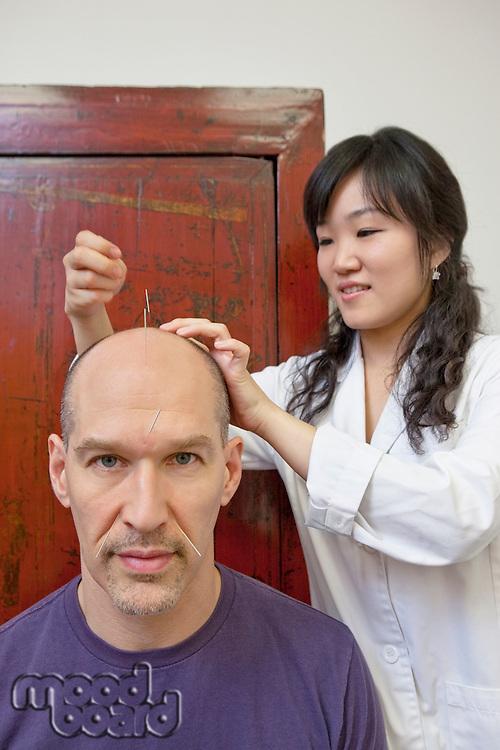 Asian female acupuncturist giving mature man Japanese treatment