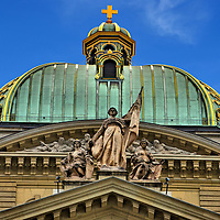 Federal Parliament Dome Statues in Bern, Switzerland<br /> On top of the Federal Parliament Building's ribbed copper dome is a gilded cross that represents Switzerland.  In front of the circular pediment with the dentil ornamentation is a statue of three females.  On the left is the executive branch, in the middle is political independence, and on the right is the legislative body.  They were sculpted by Rodo von Niederhäusern.