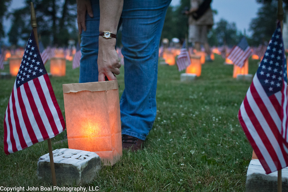 "Volunteer, Kathy Chadwick, lights luminarias at the Soldiers National Cemetery, during the Sesquicentennial Anniversary of the Battle of Gettysburg, Pennsylvania on Sunday, June 30, 2013.   Following ""A New Birth of Freedom"" program at Meade's Headquarters, a procession by candlelight was led to the cemetery. John Boal photography"