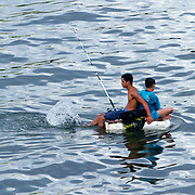 Fishermen use homemade styrofoam floating devices as boats. Fishing is not only a favorite pastime for Cubans but it is also an income source. Fishermen looking for a catch near the mouth of the river Almendares.   Photography by Jose More