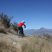 A competitor in action during the New Zealand South Island Downhill Cup Mountain Bike series held on The Remarkables face with a stunning backdrop of the Wakatipu Basin. 150 riders took part in the two day event. Queenstown, Otago, New Zealand. 9th January 2012. Photo Tim Clayton