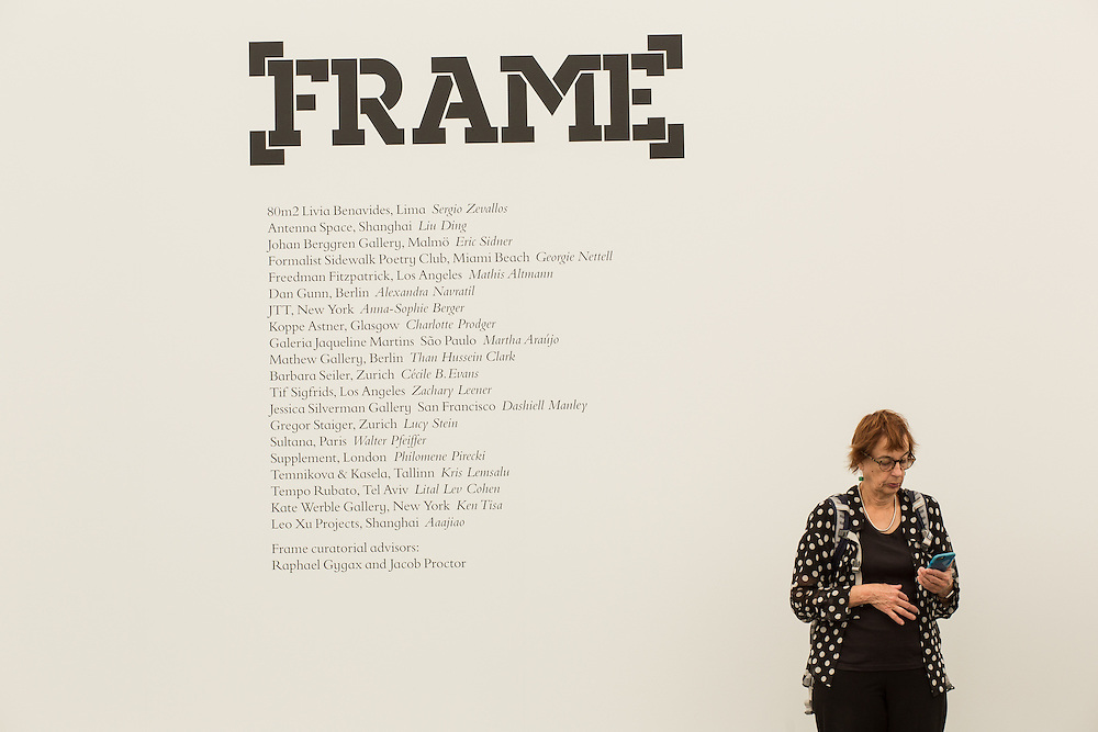 A woman checks her phone outside the area for Frame, a part of the show dedicated to galleries less than 8 years in business and presenting solo shows.