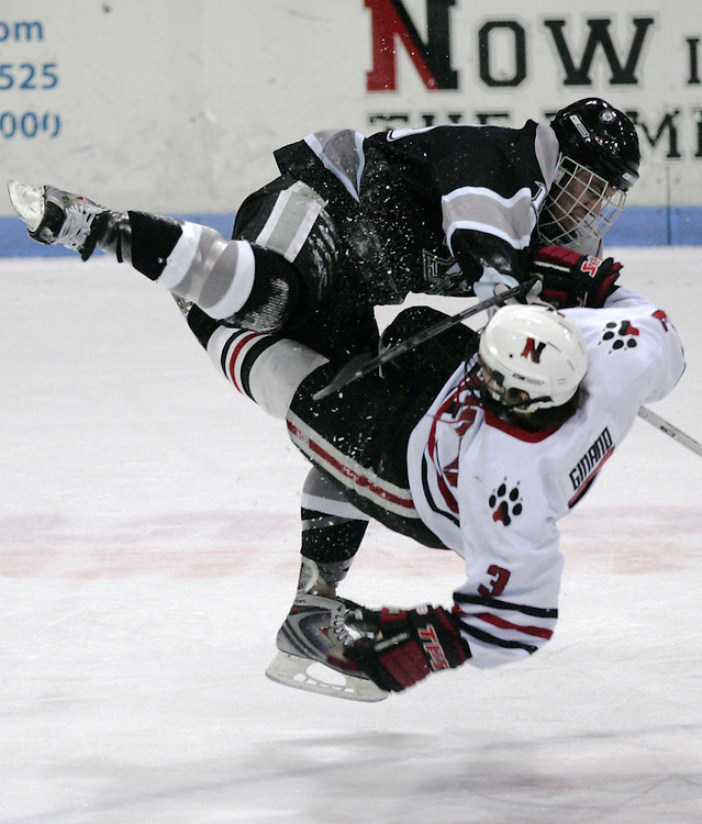 (Boston, MA - 012409) - NEHOCK - Providence forward Austin Mayer upends Northeastern forward Ryan Ginand at mid ice in the first period. Northeastern Huskies play Providence Friars in a Hockey East matchup at Matthews Arena Saturday. ..(012409nehock - Herald photo by Will Nunnally and edition)