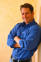 Man in a blue shirt smiling with his arms crossed