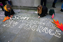 © Licensed to London News Pictures. 10/01/2020. London, UK. Protesters write a message on the pavement outside High Commission of Australia in central London as <br /> hundreds of Australians and campaigners from Extinction Rebellion climate change movement group protest against the Australian government's failure to respond to the bush fires and address the climate and ecological crisis. Photo credit: Dinendra Haria/LNP