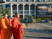 """20 JANUARY 2017 - BANGKOK, THAILAND: Buddhist monks wait to start the """"tak bat"""" (alms giving ceremony) on the plaza in front of Bangkok's City Hall. Hundreds of municipal workers and civil servants made merit by praying and presenting alms to 89 Buddhist monks Friday to mark 100 days of mourning since the death of revered Bhumibol Adulyadej, the Late King of Thailand. The significance of 89 monks is that the King, who died on October 13, 2016, was a few weeks short of his 89th birthday.        PHOTO BY JACK KURTZ"""