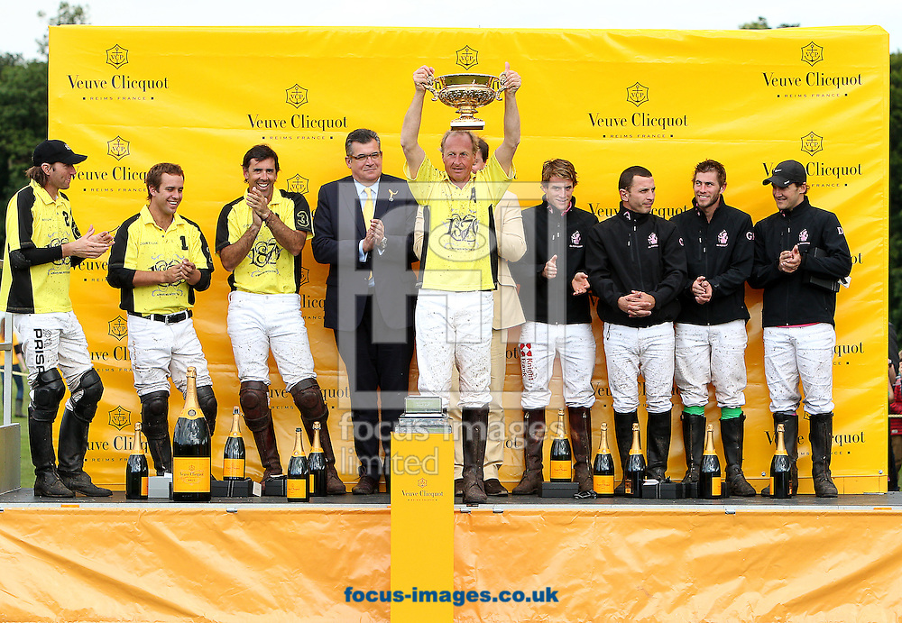 Picture by Paul Terry/Focus Images Ltd. 07545642257.15/07/12.Adrian Kirby of Cortium lifts the Gold Cup trophy after his team won the final at cowdray park polo club, west sussex.