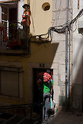 With a holy shrine on the balcony above his head, a delivery man caries a sack of potatoes into a home in Bairro Alto, Lisbon, Portugal.