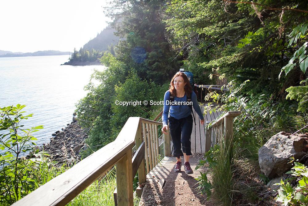 Stephanie Haynes leaving the shores of Kachemak Bay as she begins hiking up the Saddle and Alpine Ridge trail in Kachemak Bay State Park, near Homer, Alaska.
