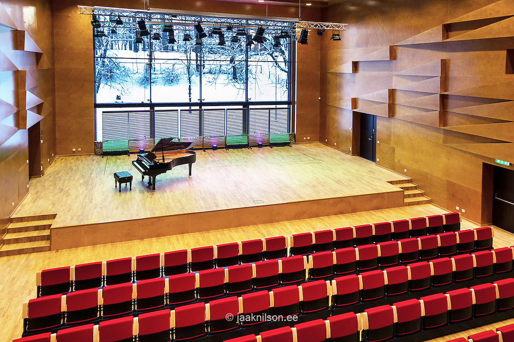 Concert hall auditorium, with rows of seats. Heino Eller's Tartu Music School in Estonia. Large window and snowy view.
