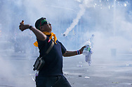 A demonstrator throws a Molotov cocktail towards the The Royal Thai Police in Bangkok, Thailand on Sunday, December 1, 2013. The week-long uprising, led by former deputy premier for the opposition Democrat party Suthep Thaugsuban, began after Yingluck attempted to pass an amnesty law that would have allowed her brother, business tycoon and former Prime Minister Thaksin Shinawatra, to return to Thailand. Shinawatra is currently living in self-exile after being overthrown in 2006.