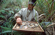February 2005 - Khe Sanh, Vietnam - A local man sells War memorabilia that he found using a home-made metal detector in the surrounding countryside around Khe Sanh. His collection ranges from old US Army dogtags, bullets to Vietcong propaganda medals. Khe Sanh was the site of a 5000 strong US Marine army base of great strategic significance for its hilltop location. The US Army located there to stop the North Vietnamese re-entering Viet Nam after travelling largely undetected through Laos. Many battles were waged here between US forces and the North Vietnamese army for control of this hill, with the largest being in 1968. The North Vietnamese Army won and captured this important location. In 1968, over 100,000 tonnes of bombs were dropped in this area alone. Photo Credit: Luke Duggleby