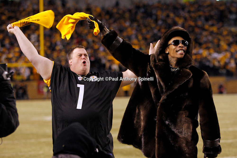 Rapper Wiz Khalifa (right) and actor Bill Gardell wave terrible towels and fire up the fans prior to the Pittsburgh Steelers NFL 2011 AFC Championship playoff football game against the New York Jets on Sunday, January 23, 2011 in Pittsburgh, Pennsylvania. The Steelers won the game 24-19. (©Paul Anthony Spinelli)