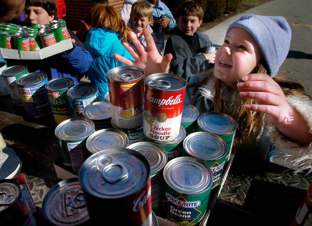 Fourth grader Katie Perzinski, right, piles canned goods in the back of a York County Food Bank truck, Thursday Feb. 9, 2006,  as the third through fifth grade students of York Country Day School complete their Martin Luther King Jr. Day volunteer project. The Lower School volunteer project collected 400 cans of food to donate to the food bank.  Students started the project by making watercolored cards, which they then sold four for $1. Using the money raised by the card sale, and donations of canned goods by the students, York Country Day was able to donate over 400 pounds of food.