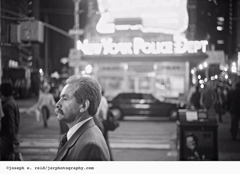 Man in profile in front of police station in Times Square at night, New York City, 2006.