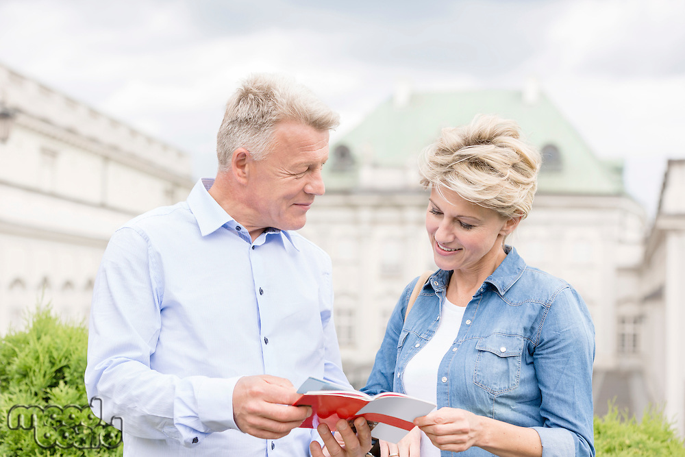 Middle-aged couple reading guidebook outside building