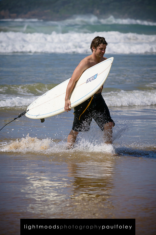 Surfer leaving the waves, Samurai Beach Port Stephens, NSW, East Coast Australia