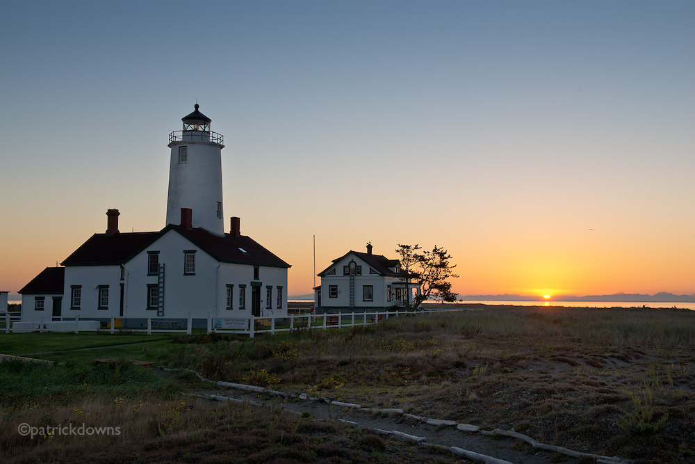 The sun rises over the Cascades across Puget Sound, seen from the Dungeness Spit Lighthouse. Sequim/Dungeness, WA.