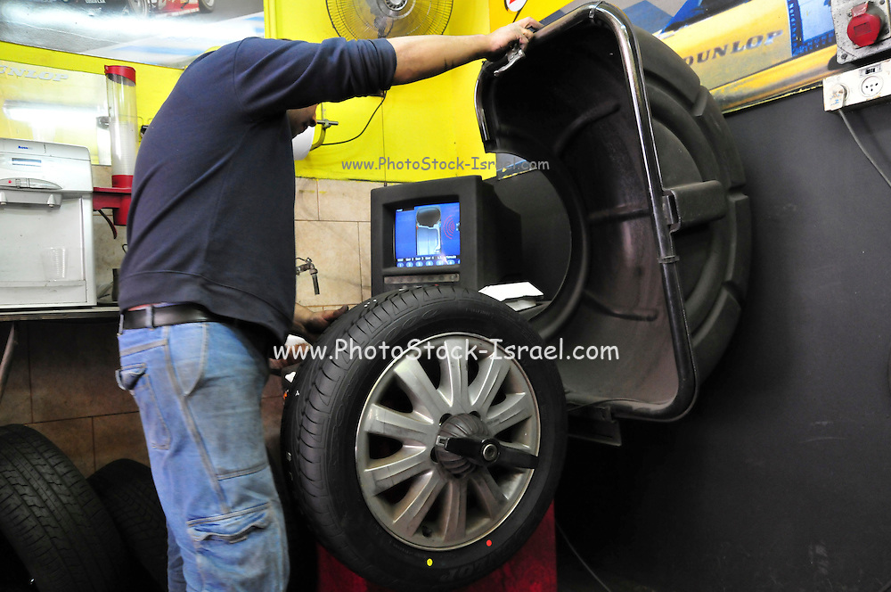 Mechanic balances a new tyre placed on a car wheel